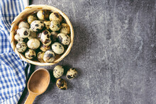 Quail Eggs In Basket And Wooden Spoon On Grey Concrete Background