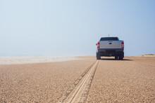 Car Parked Near Sea On Sandy Beach