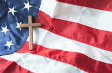 Religious Right Concept With Christian Wooden Cross On American Flag Background.  Copy Space.