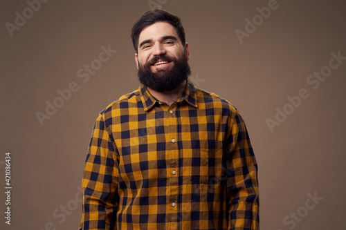 A happy man with a bushy beard is smiling at the camera and a plaid shirt Fotobehang