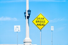 Draw Drawbridge Yellow Road Traffic Sign At Bridge Of Lions Bascule Bridge At St. Augustine, Florida From Anastasia Island Isolated Against Blue Sky In Summer