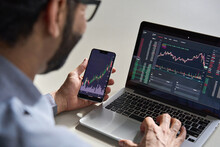 Business Man Trader Investor Analyst Using Mobile Phone App Analytics For Cryptocurrency Financial Market Analysis, Trading Data Index Chart Graph On Smartphone And Laptop Screen. Over Shoulder View