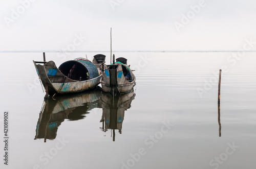 Two sampan shrimp fishing boats with a reflection in a lake between Hue and Hoi An, Central Vietnam Fototapeta