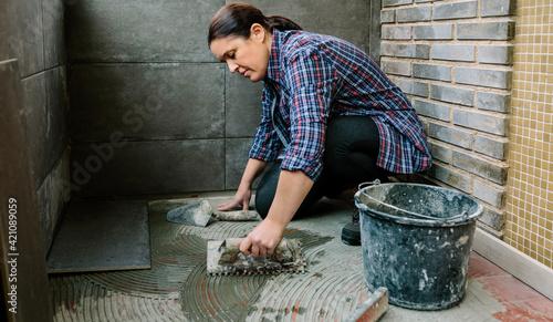 Obraz Female mason laying a new tile floor on a terrace - fototapety do salonu