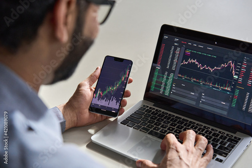 Fotografering Business man trader investor analyst using mobile phone app analytics for cryptocurrency financial market analysis, trading data index chart graph on smartphone and laptop screen