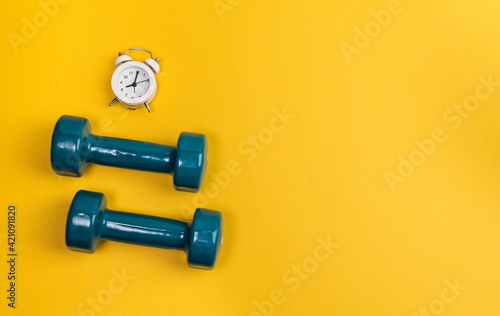 Fototapeta Dumbbell, alarm clock on yellow background. Minimalistic sport concept. Top view. obraz