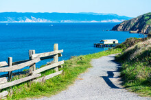 Unpaved Hiking Trail On Cliff Edge Leading To Lifeboat Station At At Point Reyes Headlands. Scenic View Of Drakes Bay Calm Blue Water And Coastline With White Sandstone Cliffs On Horizon