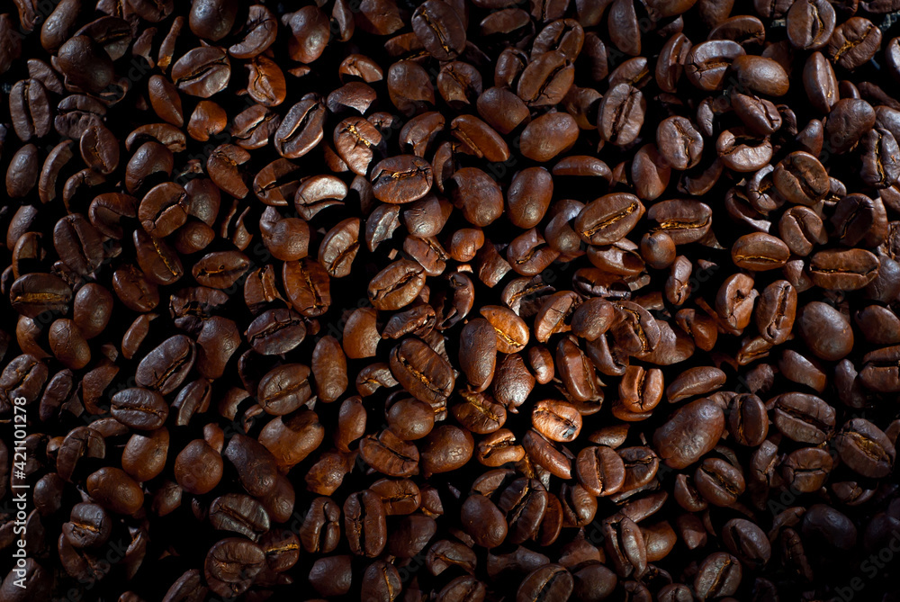Fototapeta Coffee beans close up. Texture of brown coffee beans. Contrasting dramatic light as an artistic effect.