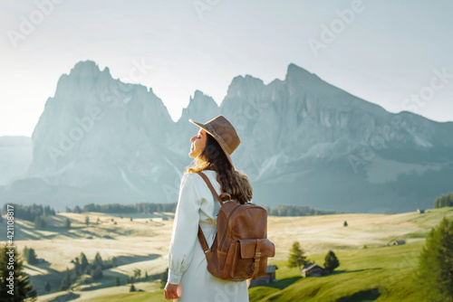 Obraz Happy young girl with white dress, hat and backpack in Alpe di Siusi, Dolomites. - fototapety do salonu