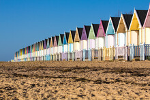 Parade Of Colourful Beach Huts On Mersea Island In Essex