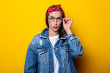 Serious Young Woman In Hair Band, In Denim Jacket With Glasses On Yellow Background.