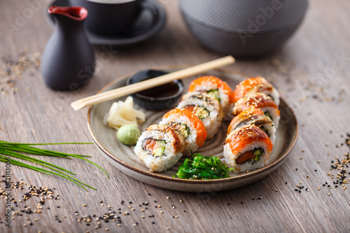 Fototapeta Sushi maki rolls with salmon, eel, avocado, cucumber on a plate with chopsticks, soy sauce, wasabi and ginger. Japanese traditional fish food closeup served for lunch in modern gourmet restaurant obraz