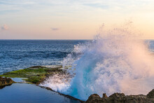 Ocean Wave Breaking On The Rocky Cliffs At Devil's Tear, Nusa Lemongan, Bali, Indonesia. Blue-green Water, White Spray In The Air. Tidal Pool In Foreground On Top Of Cliff. Pacific Ocean Behind.