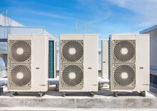 Condenser Unit Or Compressor On Roof Of Industrial Plant Building With Sky Background. Unit Of Central Air Conditioner (AC) Or Heating Ventilation Air Conditioning System (HVAC). Pump And Fan Inside.