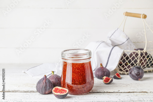 Jar of sweet fig jam on white wooden table
