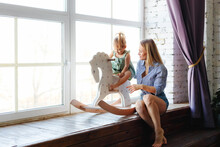 A Young Mother In Denim Shorts And Her Cute Little Daughter On A Rocking Horse Are Sitting At The Window On A Wooden Sill.