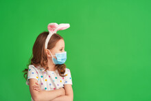 Cute Little Girl Wearing Easter Bunny Ears And Mask Standing On Green Background On Easter Day. Child Is Happy And Celebrates Easter Exactly According To The New Rules. Protection From Coronaviruses