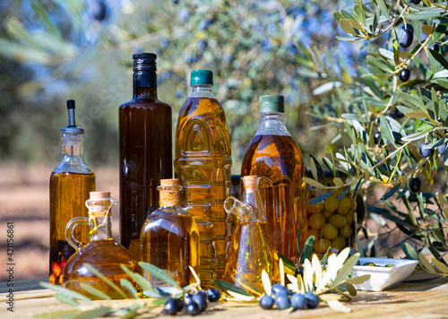 Fototapeta Glass bottles and carafes with fresh olive oil on wooden table on background wit