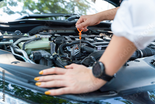 Obraz Close up hand of woman check the oil level in car engine. - fototapety do salonu