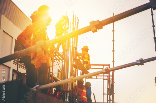Fotografie, Obraz Construction workers in safety uniform install reinforced steel scaffolding at outdoor construction site