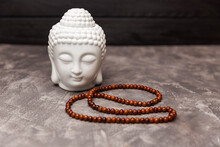 Ceramic Head Of Buddha Statue. Buddha Figurine Decorative Head. Copy, Empty Space For Text. Scandinavian Style. Close Up Of A Buddha Figurine And Smoky Incense With Rosary. Old Antique Chinese Budha.