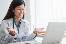 Asian Therapist Woman Doctor Is Online Visiting With A Patient On The Internet Application. Her Listening And Give Advice And Explains How To Treat The Initial Disease, Concept Of Medical Technology.