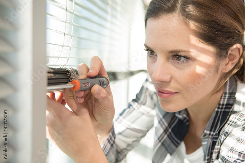 Obraz woman repairing a window blind with a screwdriver - fototapety do salonu