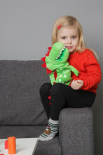 Cute 3 Years Old Girl Playing With Hand Plush Puppet Dinosaur. Soft Educational Toy For Creativity And Emotional Development.