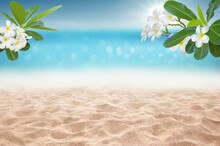 Focus Area At Sandy Beach  And Bokeh Sun Light On Blurry Sea With Plumeria Flower Branch Tropical Summer Time Concept Background