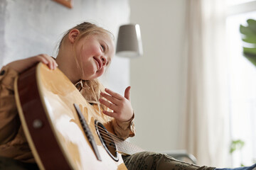 Low angle portrait of cute girl with down syndrome playing guitar and smiling happily, copy space