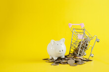 White Piggy Shopping Cart With Coins Thai Baht On Yellow Background, Save Or Investment Concept.