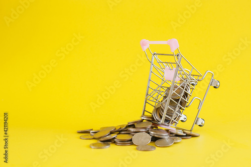 Valokuvatapetti Shopping cart with coins thai baht on yellow background, save or investment concept
