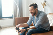Portrait of young bearded hipster guy sitting on the couch in the living room, holding joystick, screaming, and winning a video game match, male addicted gamer with an open mouth is about to succeed