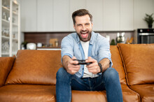 Front View Of Young Bearded Hipster Man Sitting On The Couch In The Living Room Staying At Home And Playing, Holding Wireless Joystick, Screaming, And Winning Intense Video Game Match, Victory Concept