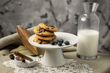 Horizontal Capture Of Chocolate Chip Cookies Lined Upwards With Bottle Of Milk, Blueberries, Cinnamon Bark In Wooden Plate And Lace Ground In Frame