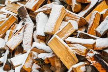 Stacked Firewood Covered With Snow. A Woodpile Of Dry Fire Woods In The Winter. Winter Fire Wood Provisions.