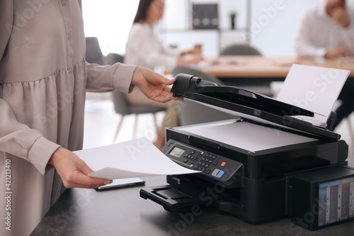 Canvas Print Employee using modern printer in office, closeup