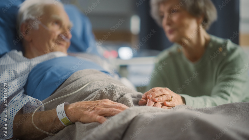 Fototapeta Hospital Ward: Focus on Hands of Elderly Man Resting in Bed, His Caring Wife Supports Him By Sitting Beside and Comforting with Her Touch. Old Man Recovering successfuly after Sickness and Surgery
