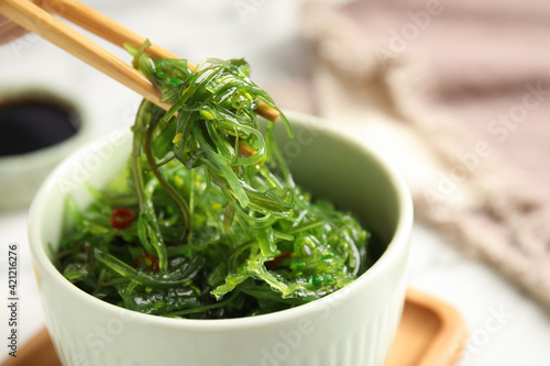 Fototapeta Chopsticks with Japanese seaweed salad in bowl on table, closeup obraz