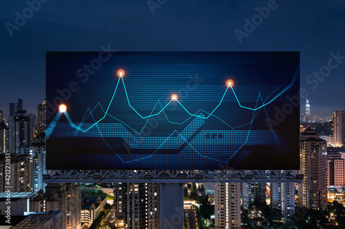 FOREX graph hologram on billboard, aerial night panoramic cityscape of Kuala Lumpur. KL is the developed location for stock market researchers in Malaysia, Asia. The concept of fundamental analysis