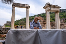 A Bald Man With Protective Mask Standing And Looking Between Two Historical Gates In Architecture Field