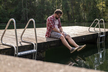 Upset Man Sits On The Edge Of A Wooden Pier And Gazes Thoughtfully Into The Water. Lifestyle.