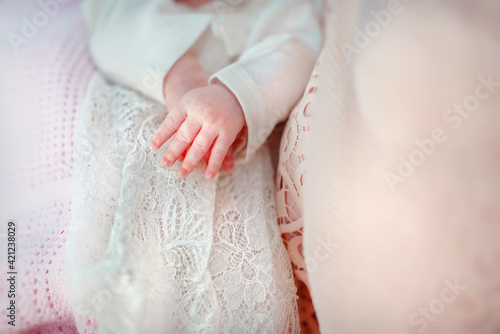 handles of a newborn baby in a beautiful baptismal dress Fototapet