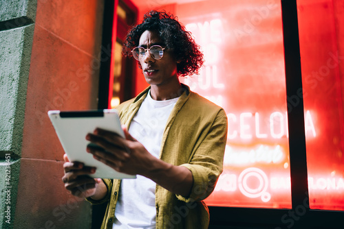 Serious handsome hipster guy in eyewear holding digital tablet connected to 4G internet connection, pensive trendy dressed male using touchpad for share media multimedia content on neon lights