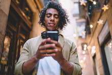 Handsome Young Male With Curly Hair Using Mobile Phone For Sending Messages And Text Email, Hispanic Hipster Guy Searching Web Publication During Wireless Browsing Via Smartphone Application