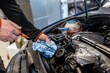 Mechanic in a car repair shop checking the oil in a vehicle