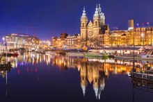 Amsterdam, Netherlands City Center View With Riverboats And The  Basilica Of Saint Nicholas