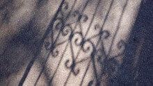 High Angle View Of Gate Shadow On Street