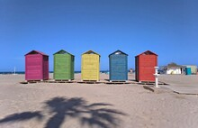 Beach Huts Against Buildings Against Clear Blue Sky