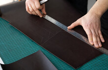 Men S Hand Holding A Stationery Knife And Metal Ruler And Cutting On A Pieces For A Leather Wallet In His Workshop. Working Process With A Brown Natural Leather. Craftsman Holding A Crafting Tools.